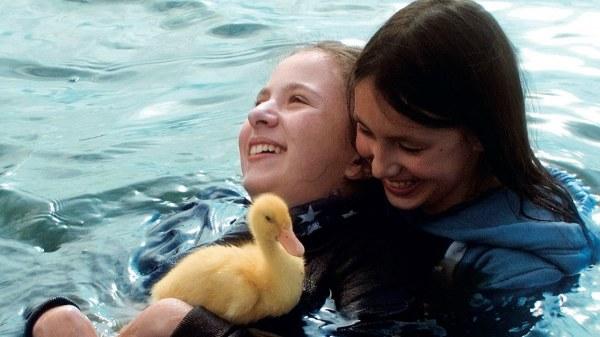 Ein Mädchen zieht anderes Mädchen durchs Wasser, im Vordergrund ein Entenküken